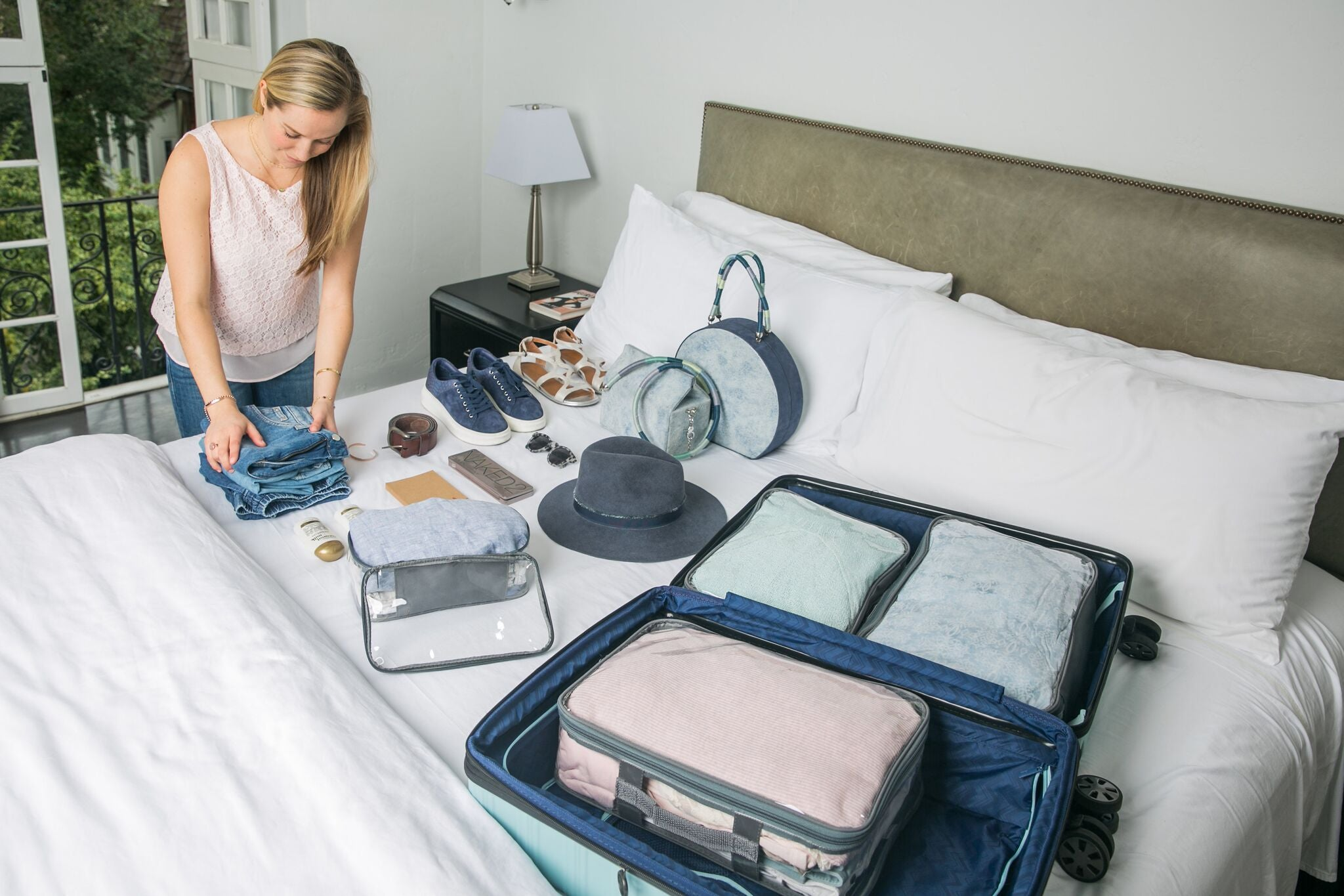 Woman organizing suitcase using packing cubes