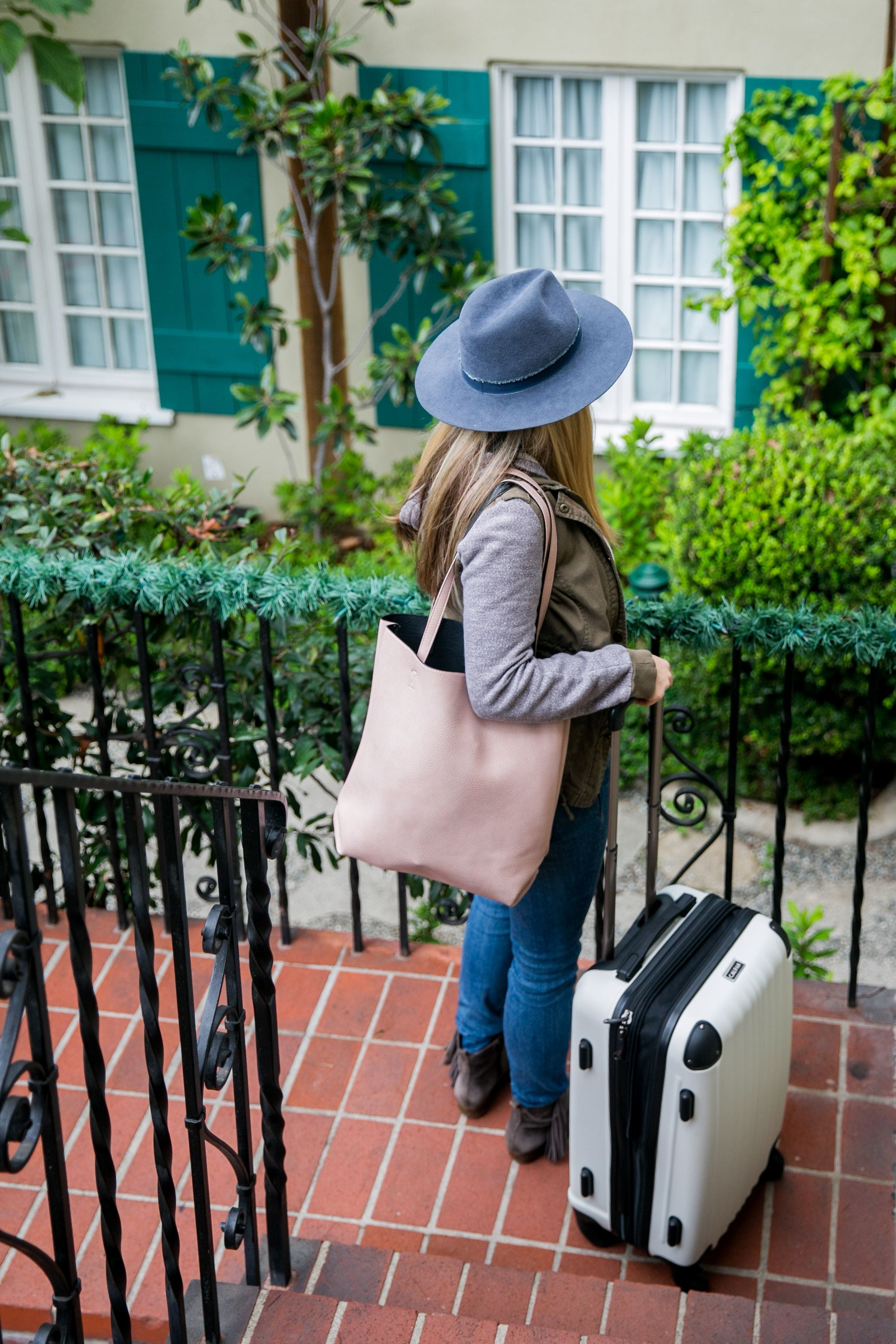 Lady packed and ready to travel with a tote bag and carry on suitcase