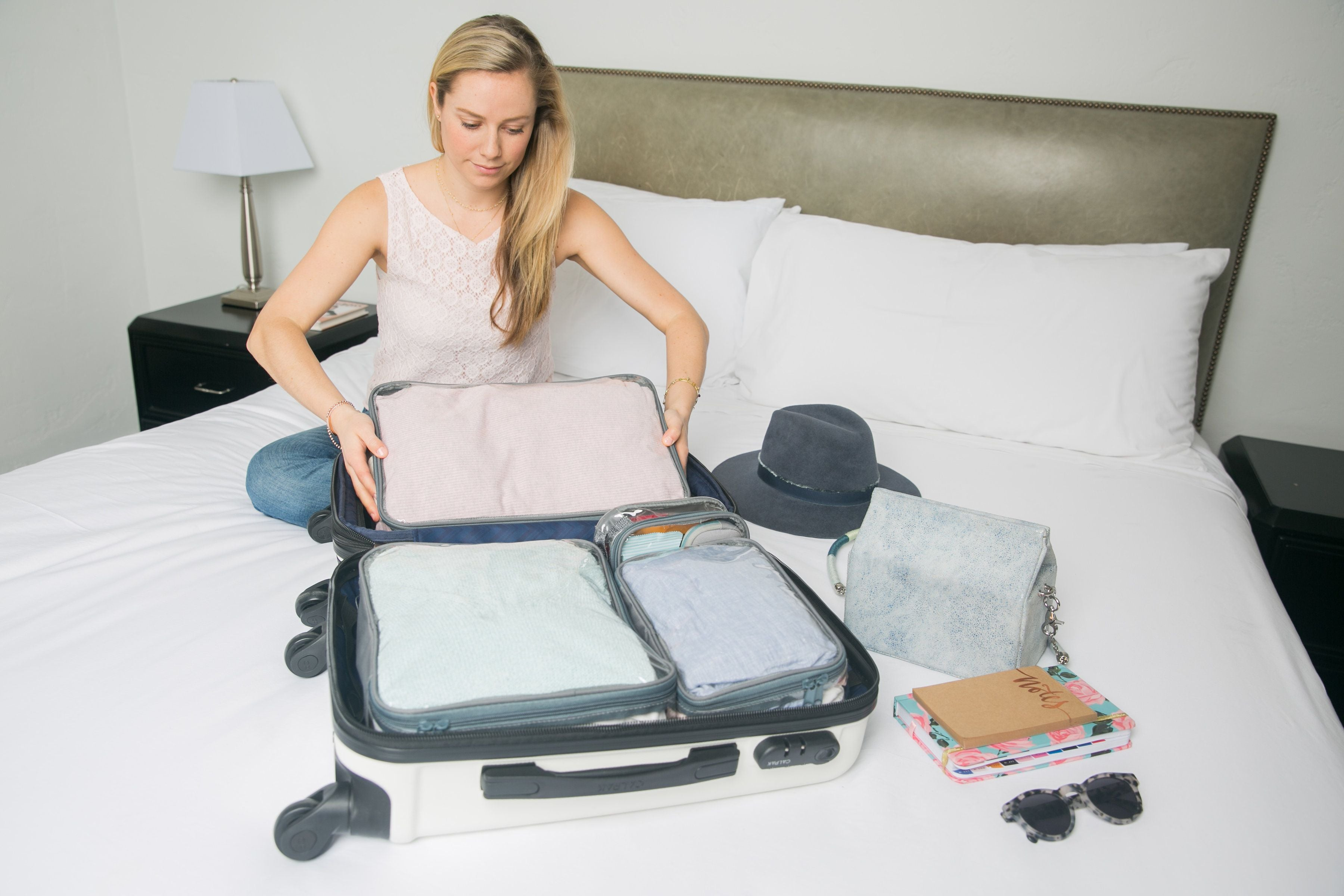 Lady packing starter set in a carry-on suitcase