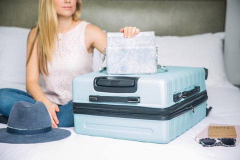 Blonde haired woman holding light blue cute suitcase for all your travel essentials