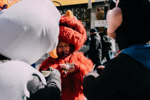 Little boy wearing Elmo costume counting money to buy tickets