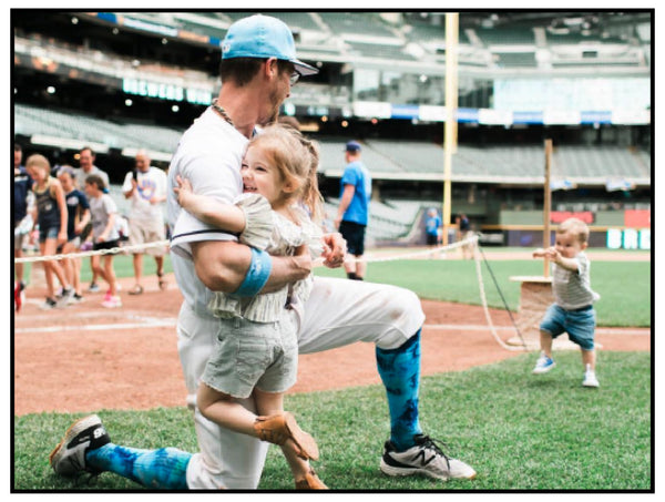 Baseball player hugged by daughter in playing field