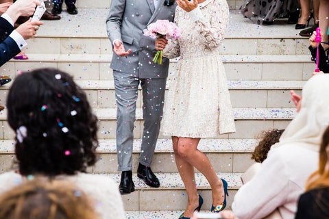 Newlyweds on stairs with confetti thrown by guests