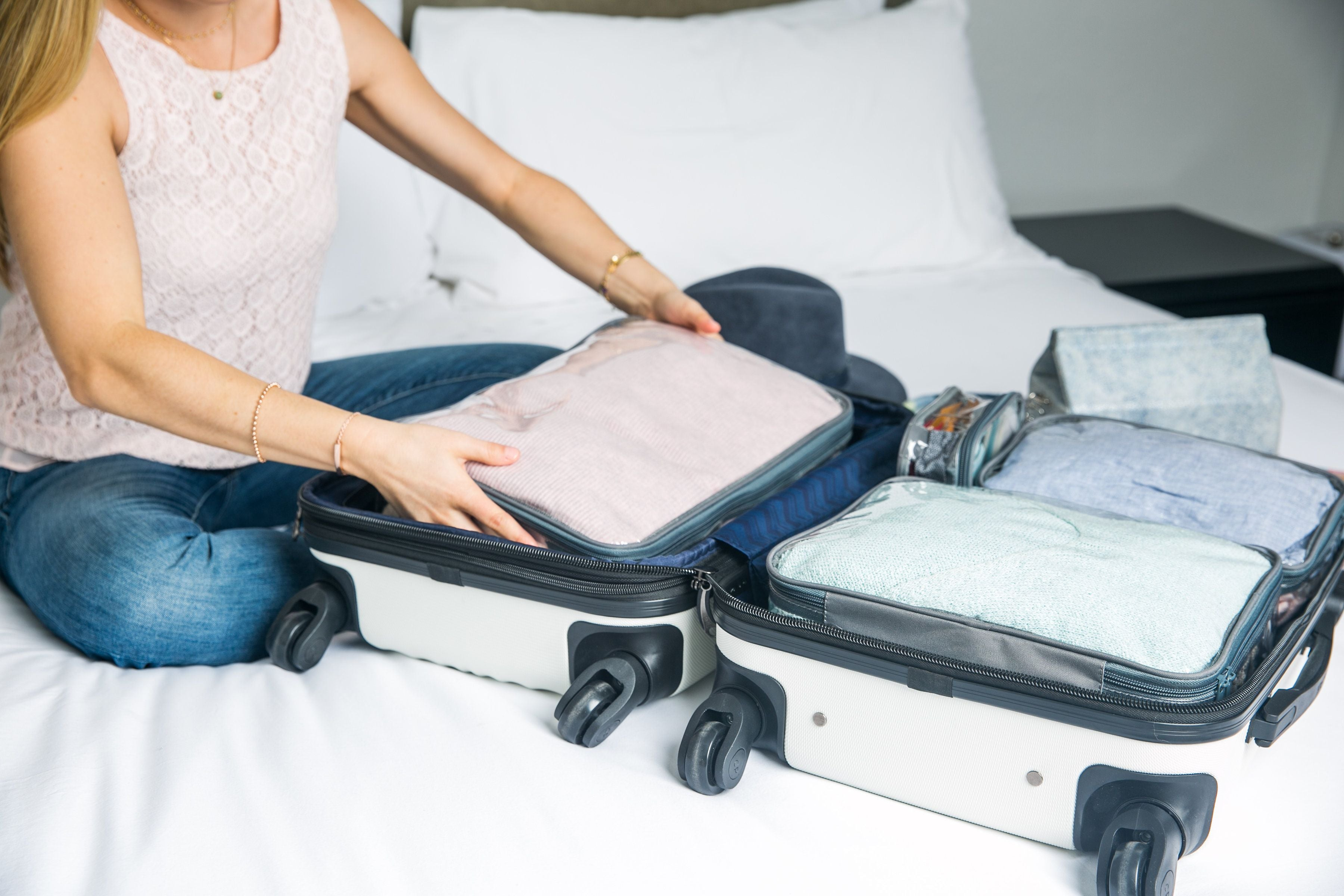 Woman using packing cubes to organize suitcase