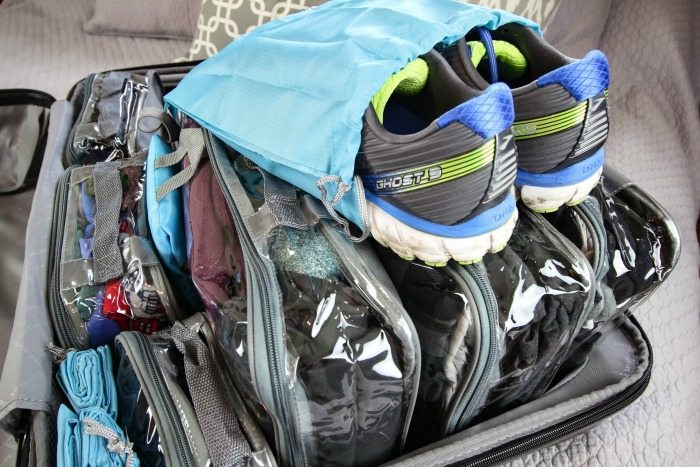 Pair of shoes in a travel shoe bag on top of suitcase