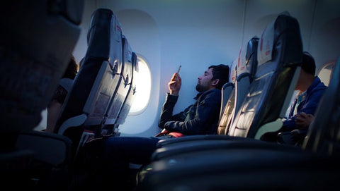 Man using smartphone while on flight