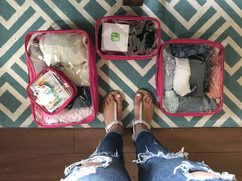 Pink packing cubes with essential travel items