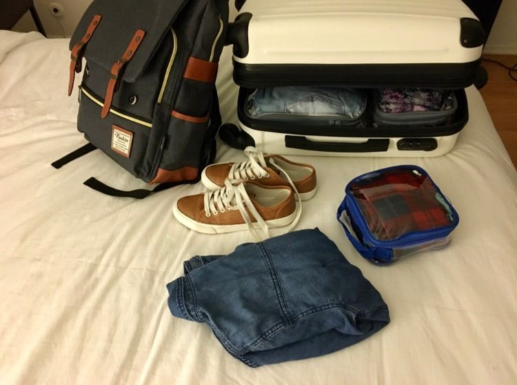 Shoes, backpack, carryon suitcase and other travel items on the bed