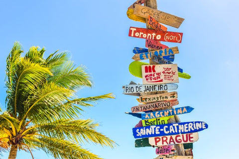 Colorful signs pointing to different popular overseas travel destinations