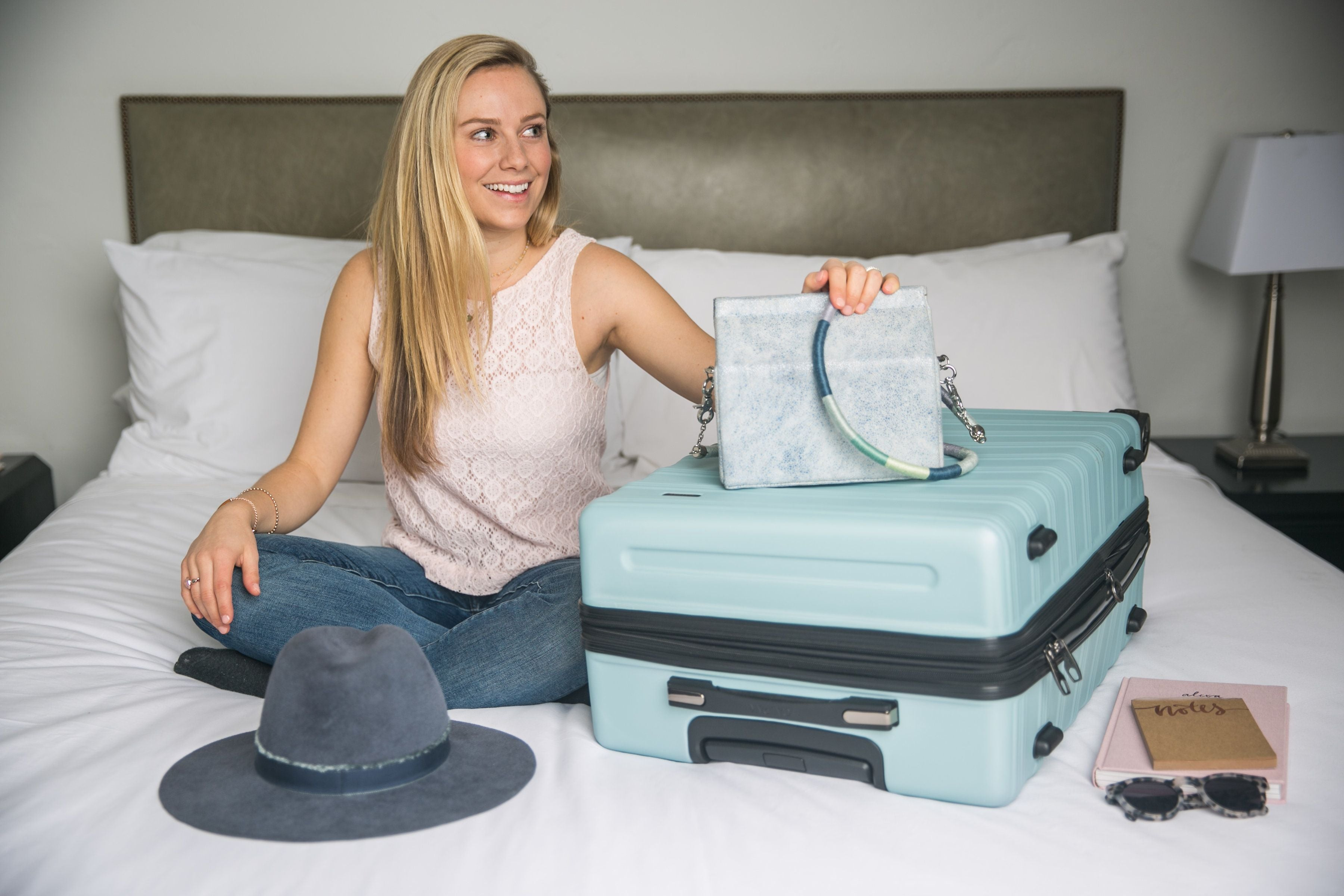 Smiling woman with purse and hard shell suitcase