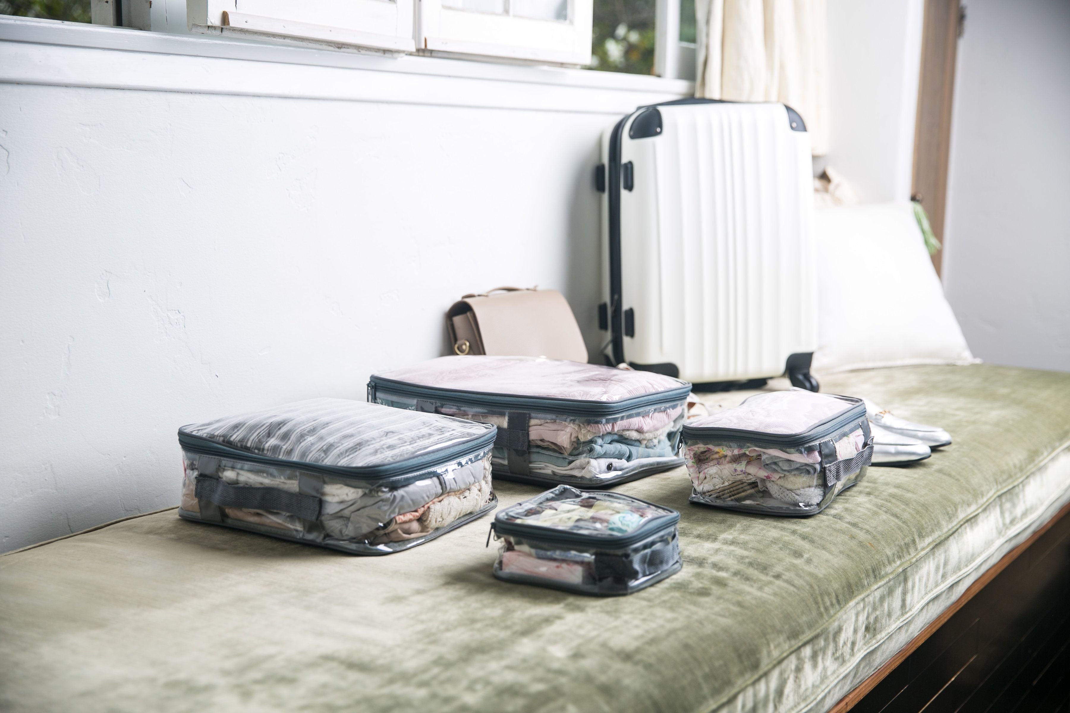 Starter set packing cubes and a white hard shell suitcase
