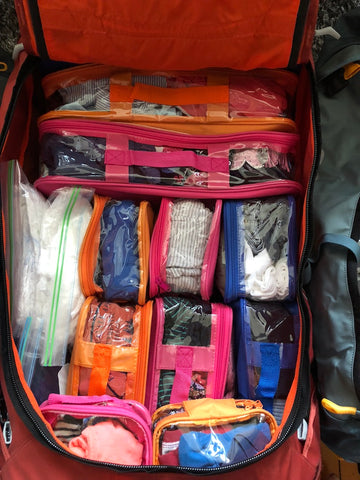 Pink and orange color coded packing cubes for kids inside suitcase