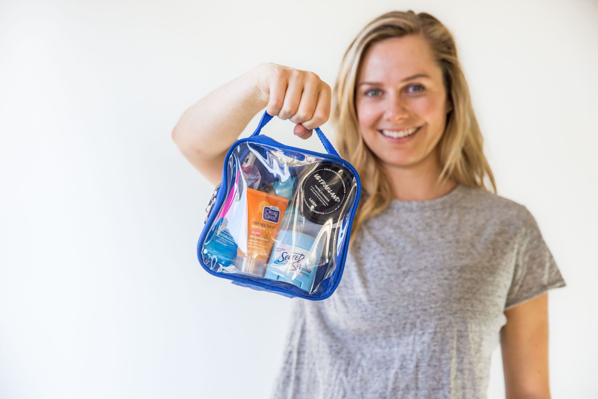 Tali holding a royal blue quart size bag packed with toiletries