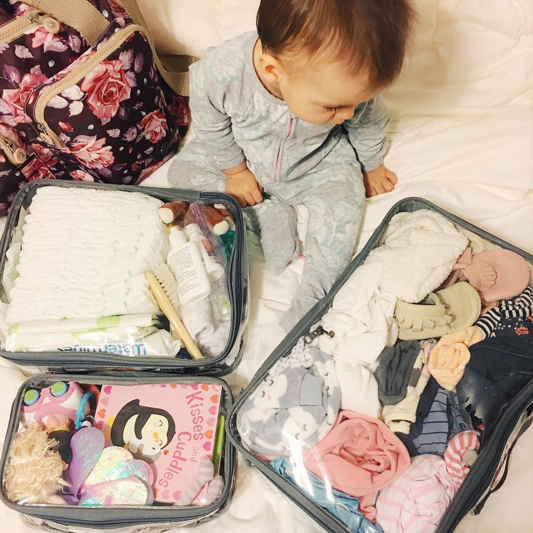 Baby essentials for flight organized in clear packing cubes
