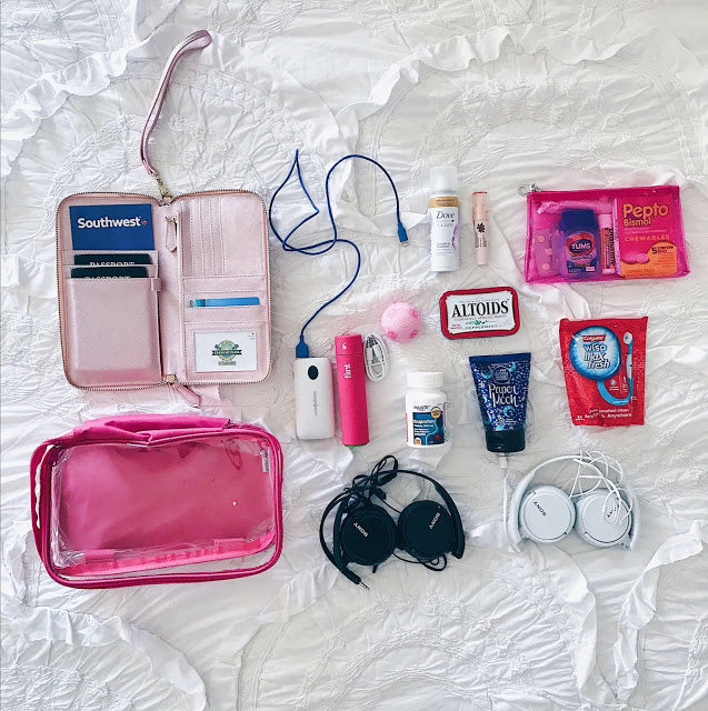 Travel essentials in a small pink cube