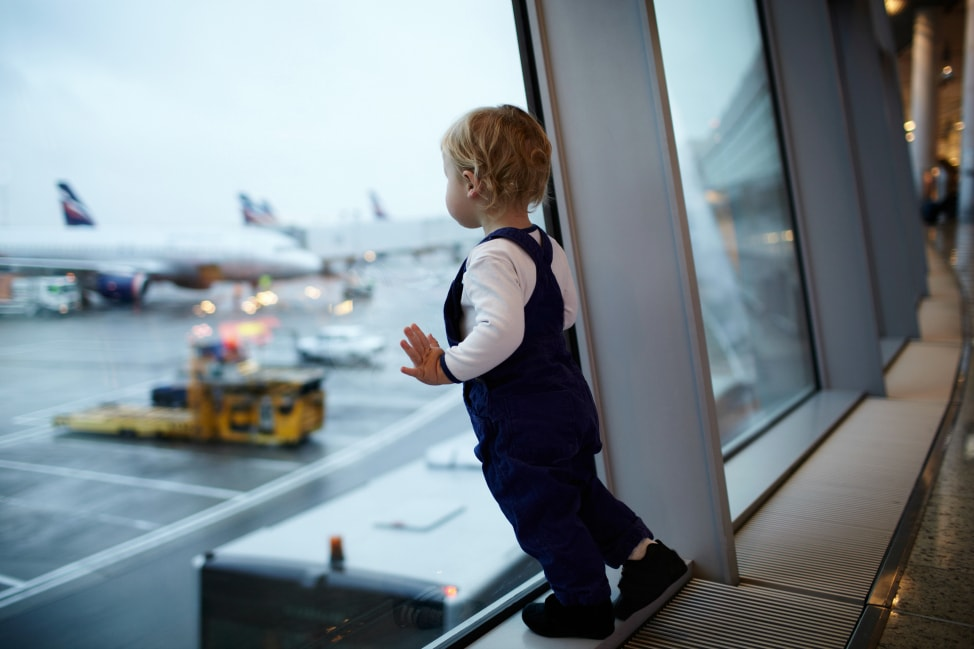 Cute baby looking out from airport glass walls