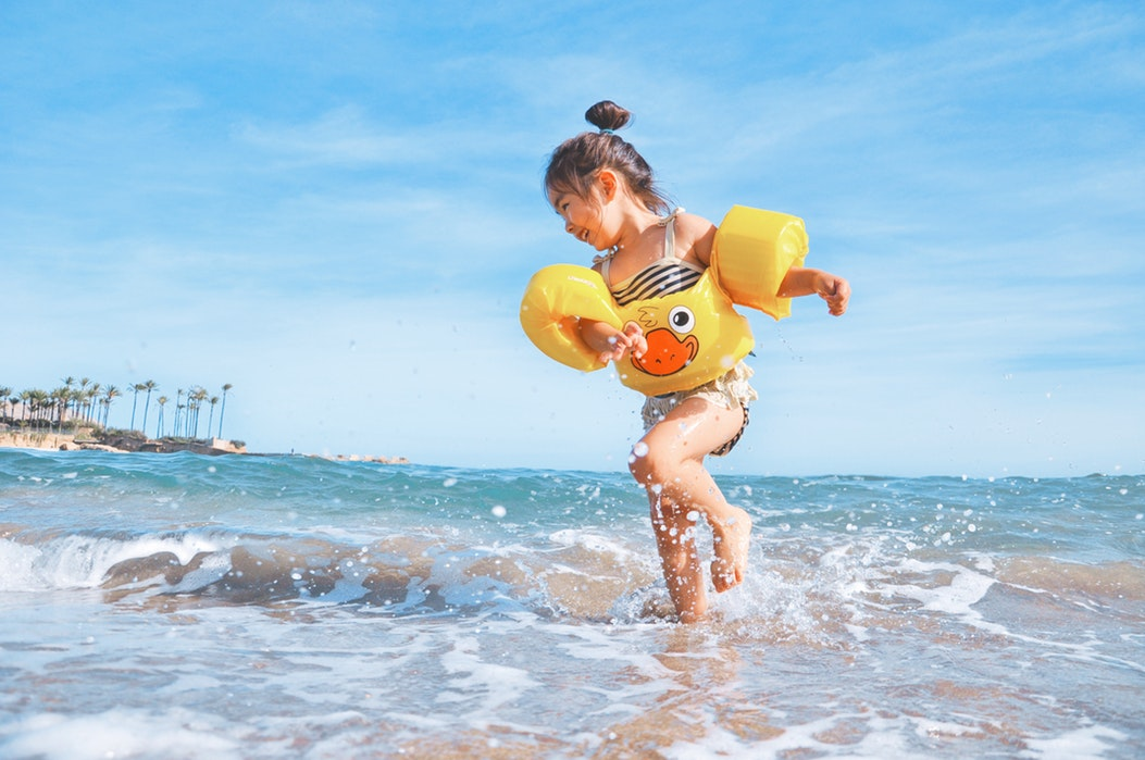 Toddler wearing swimsuit splashing on the beach