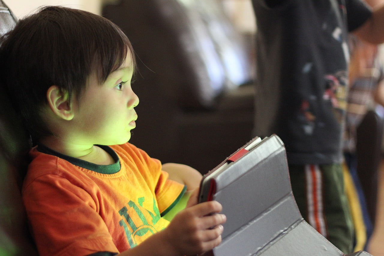 Toddler playing with tablet during red-eye flight