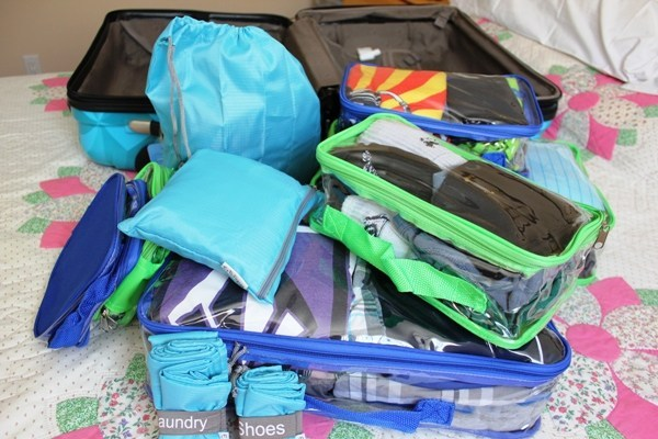 Travel essentials packed in clear packing cubes and extra empty bag