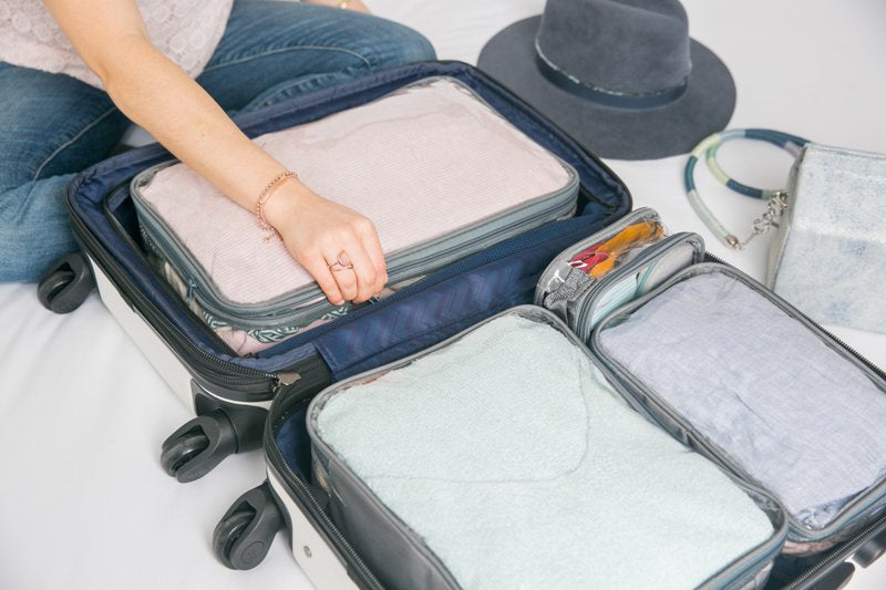 Woman using EzPacking Starter Set for organizing luggage before going soul searching