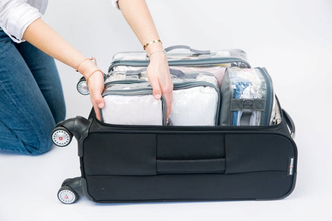 Woman packing light luggage for soul-searching journey using packing cubes
