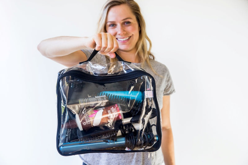 Woman holding cube with all travel hair tools and products
