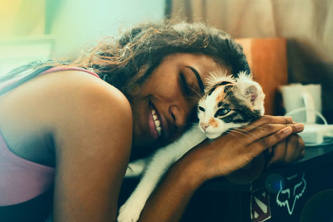 Woman cuddling pet cat before leaving for trip