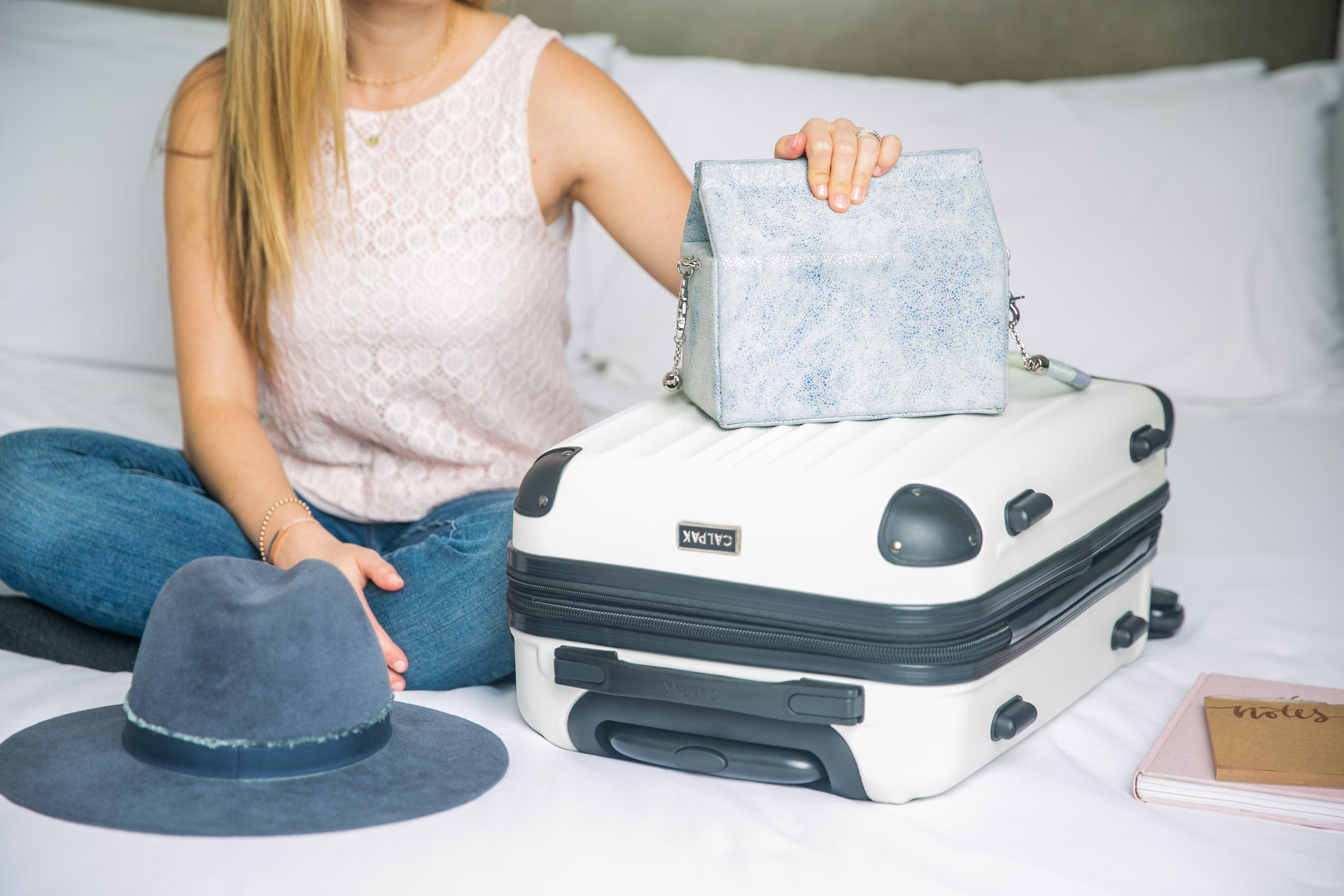 LDS Sister sitting on the bed with her packed and organized mission suitcase