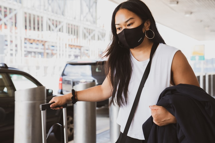 Woman wearing a mask holding a suitcase