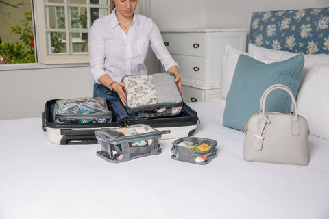 Woman putting EzPacking cubes inside luggage for organization