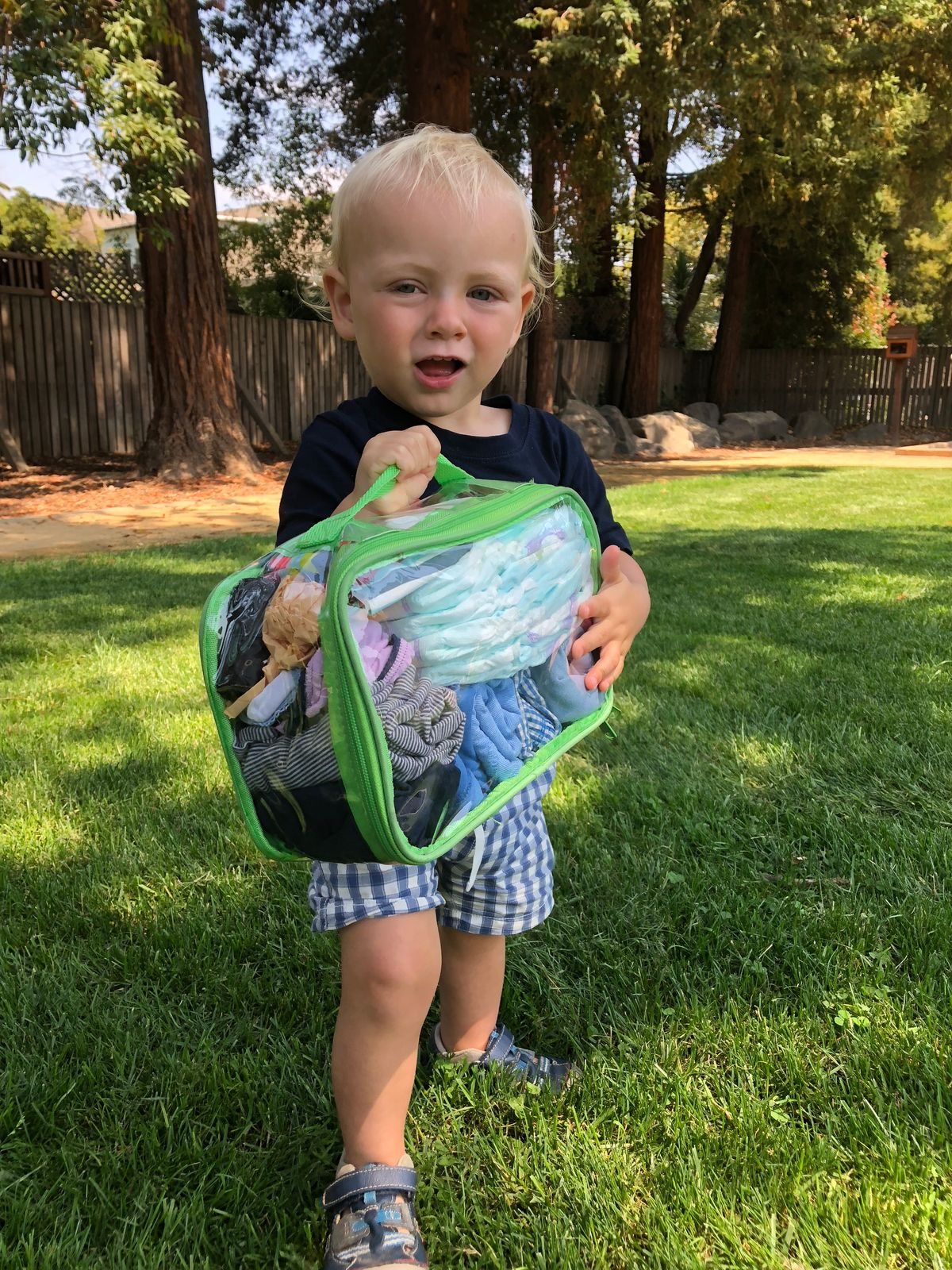 baby holding a green small cube with travel essentials