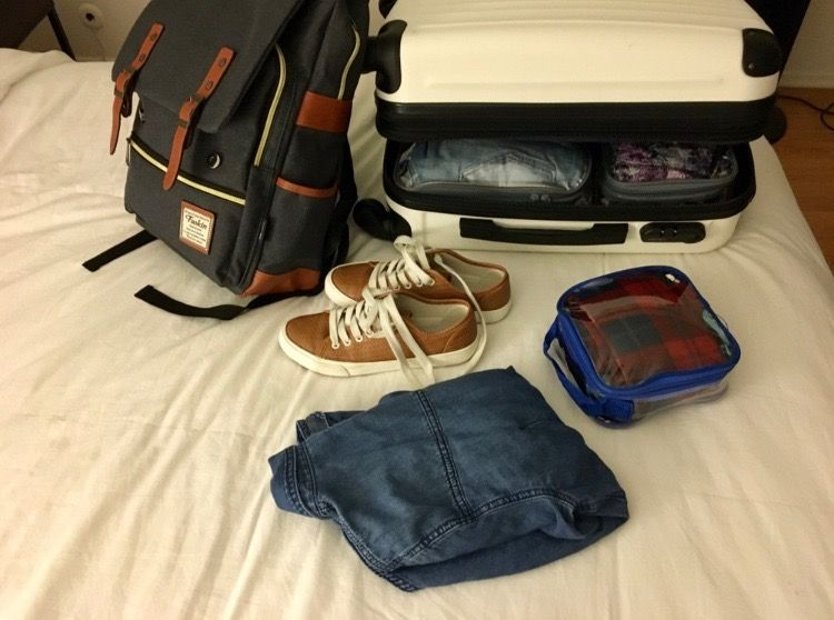 backpack, a suitcase, shoes, a jacket, and an extra small packing cube
