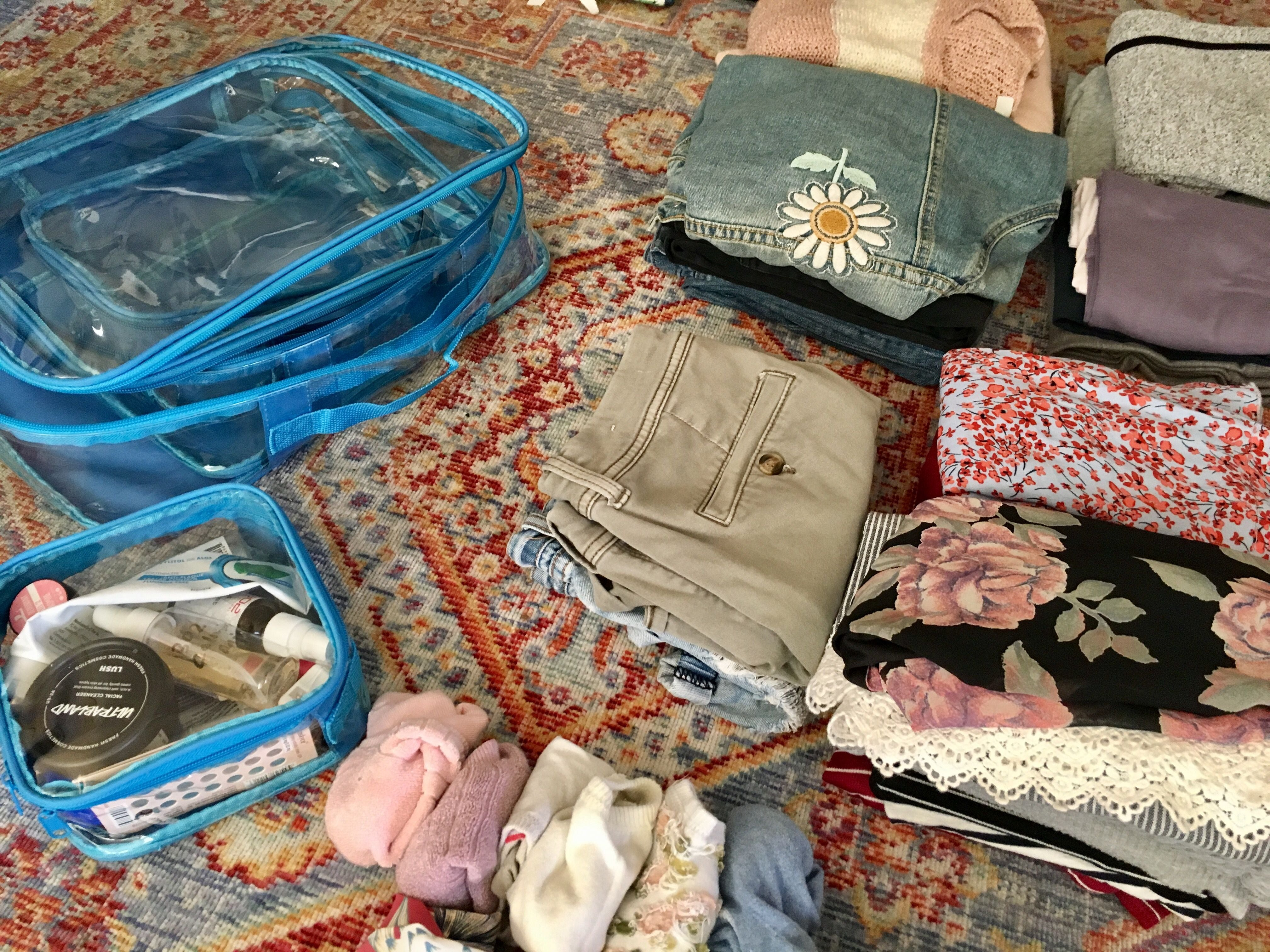 Folded clothes and turquoise clear packing cubes on the floor