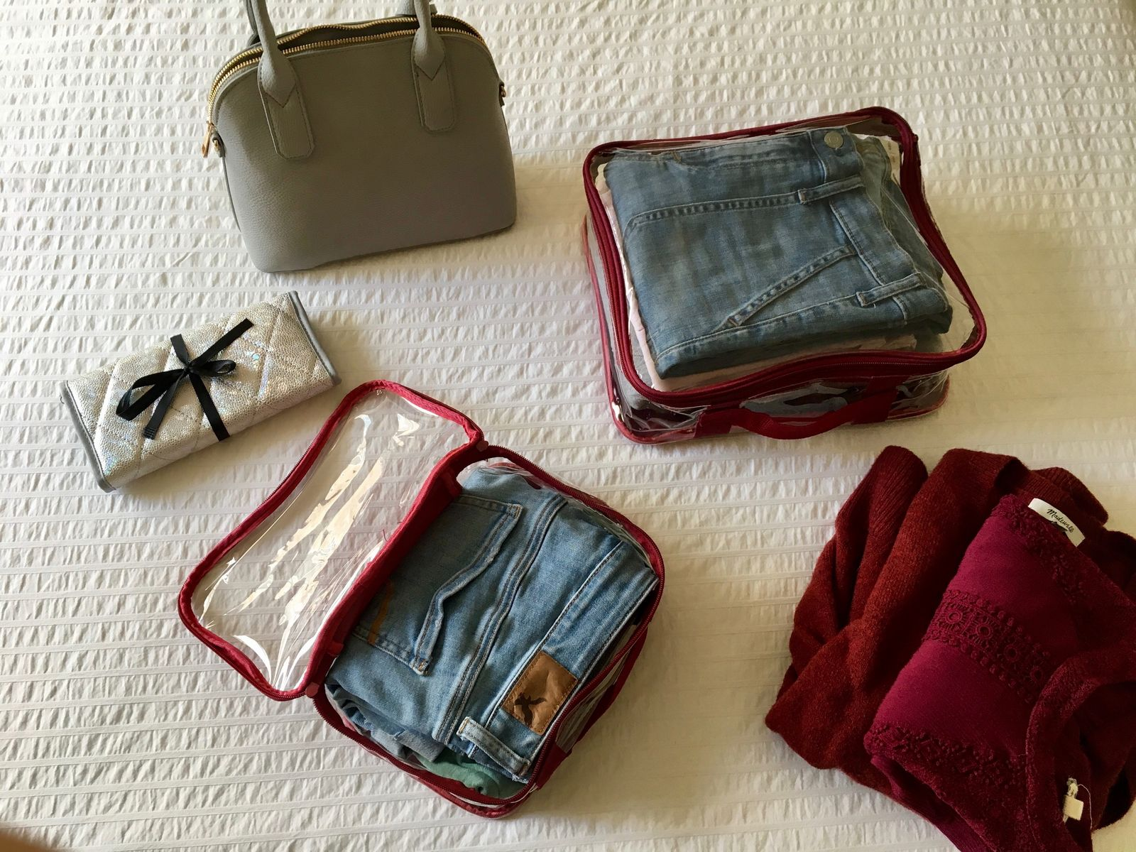 Folded jeans and shirts packed in clear packing cubes