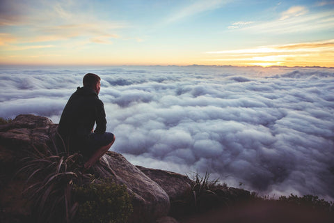 Man wearing beanie and jacket sitting on a top of a rock with a view full of clouds