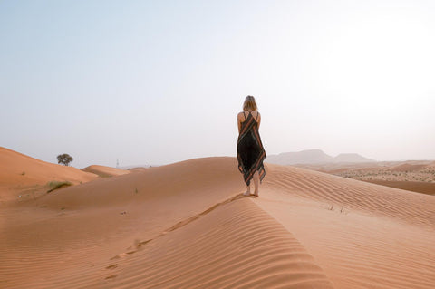Medium haired girl traveling on a desert alone on a sunny day