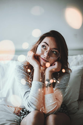 Young girl with fairy lights smiling and dreaming