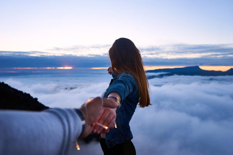 Romantic setup in clouds and fairy lights with a girl holding hands with partner