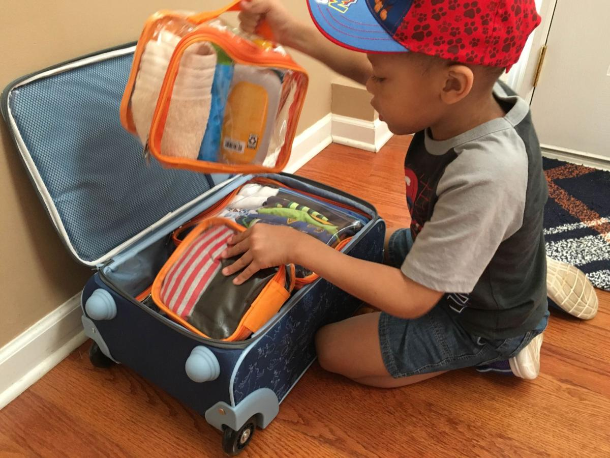 little boy and his packed suitcase with packing cubes