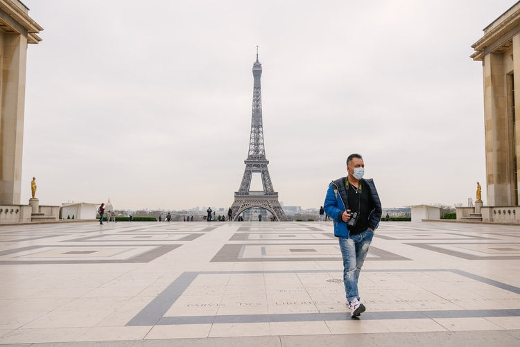 man wearing a mask walking in front of the eiffel tower on the first day of Paris lock-down
