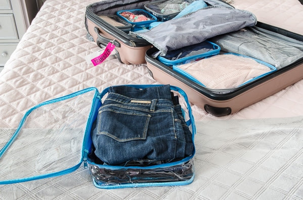 organizing travel essentials in clear packing cubes
