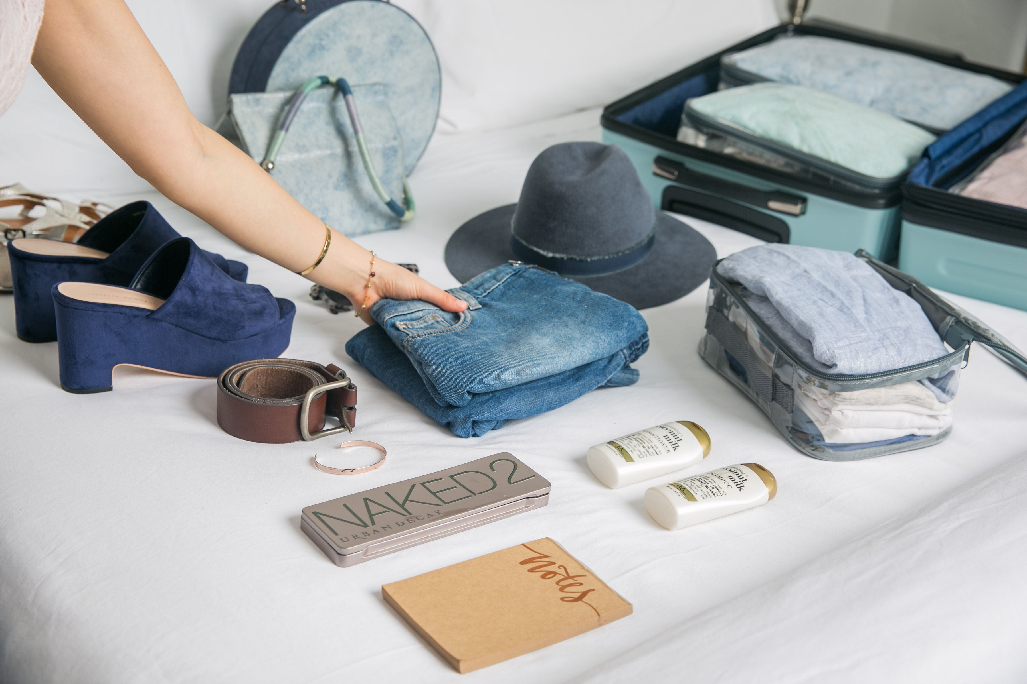 Travel essentials and jeans laid out on the bed with clear packing cubes