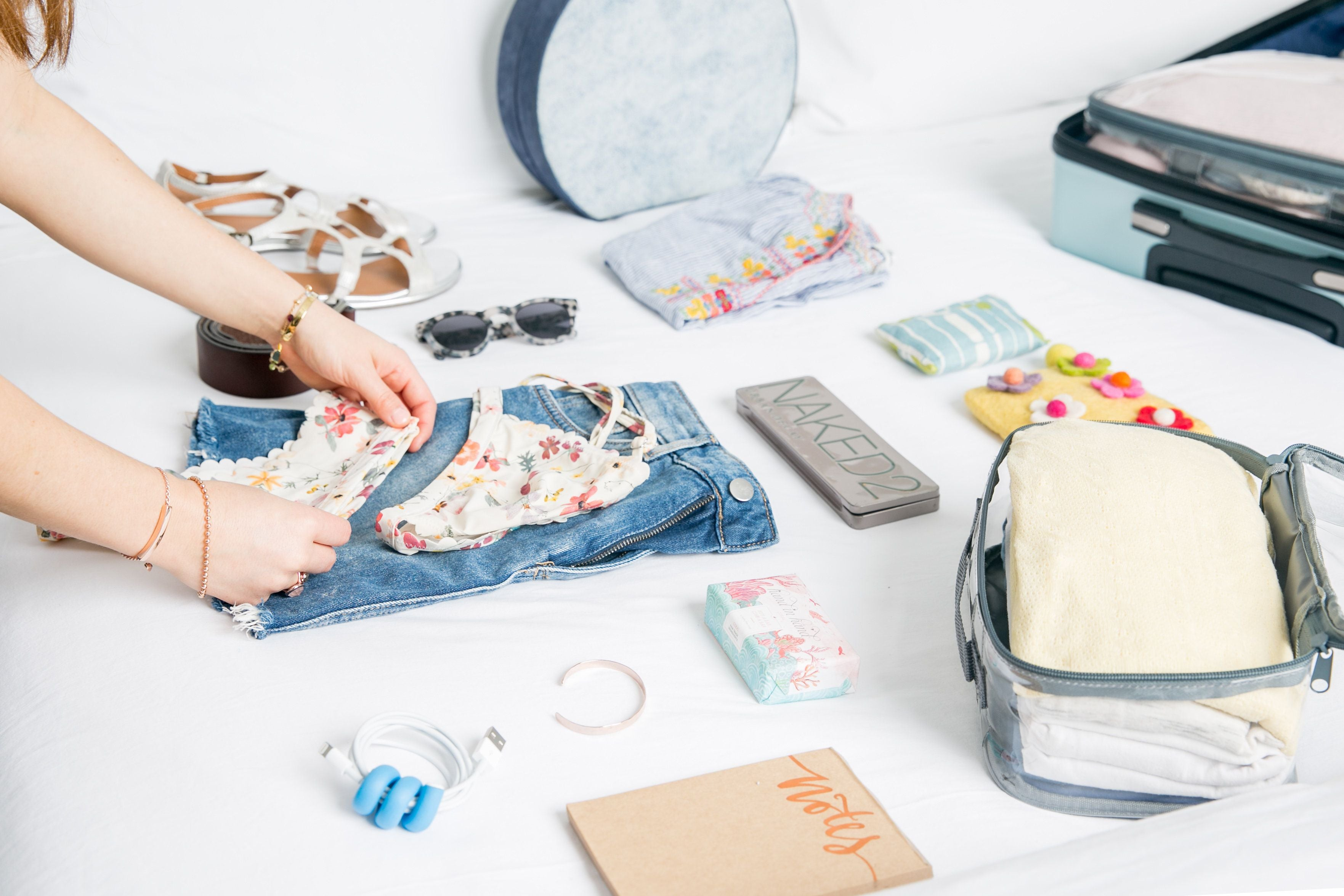packing swimsuit, shorts, and other travel essentials in packing cubes