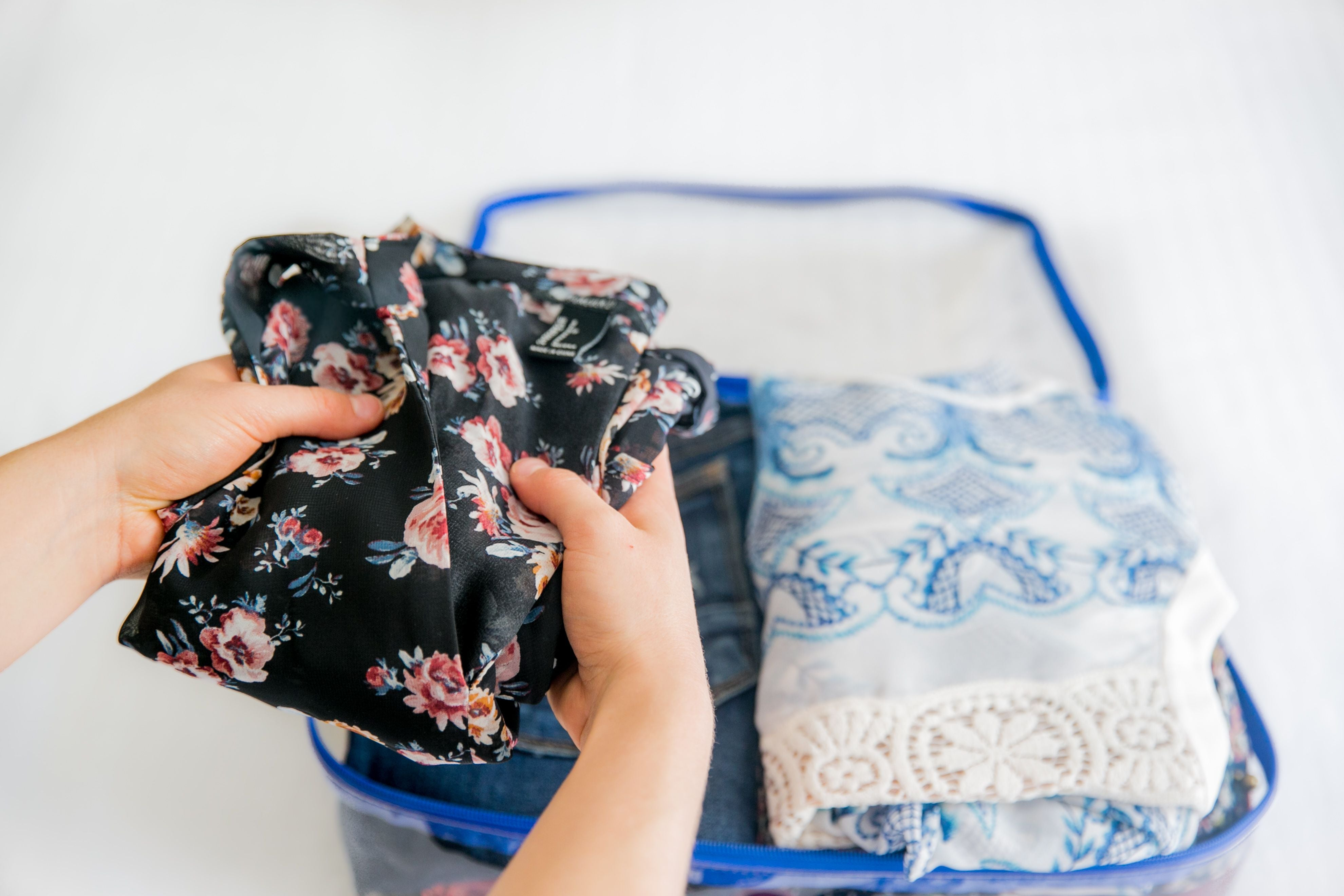 Packing women's clothes in a turquoise medium cube