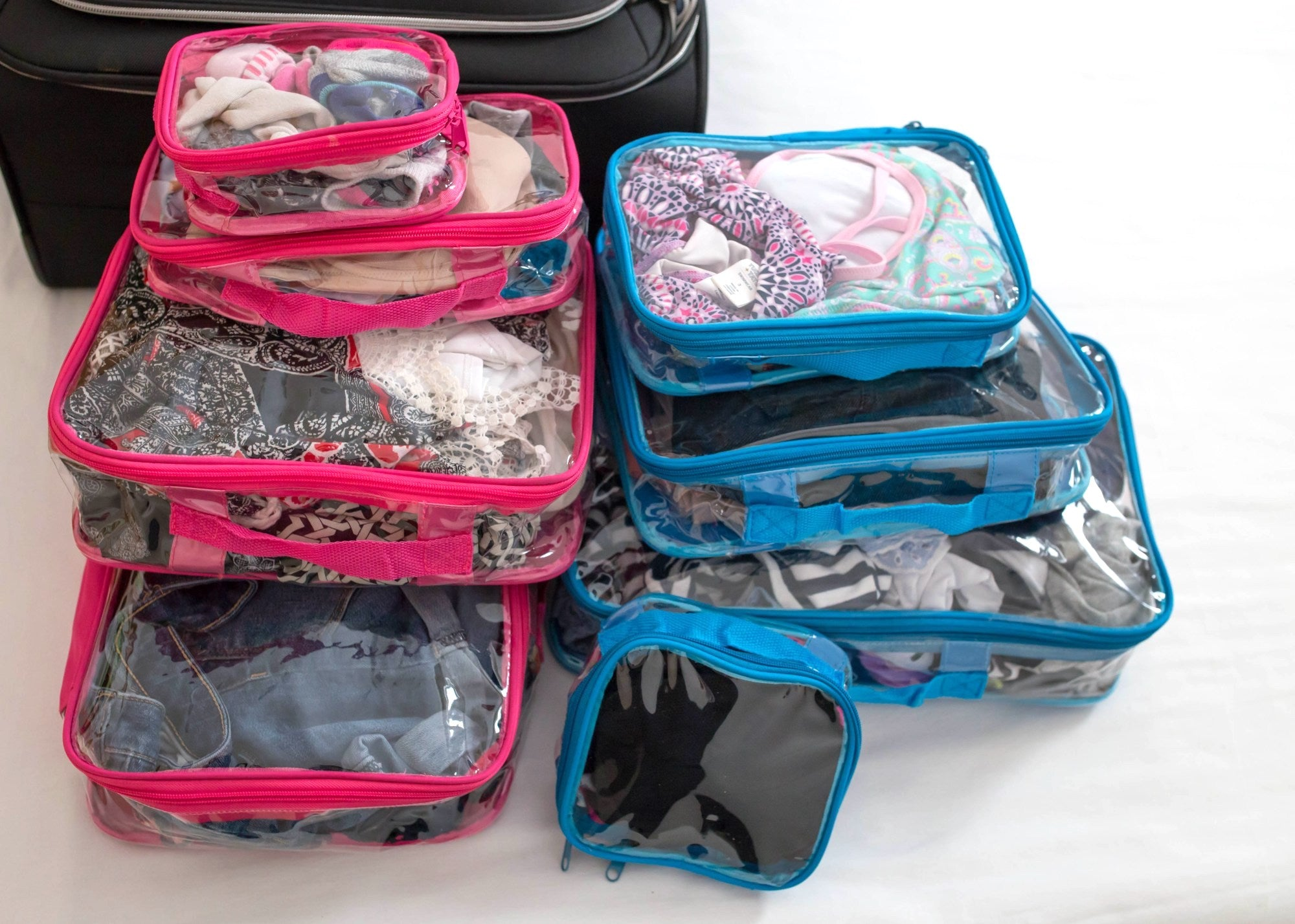 A set of pink and blue clear packing cubes for travel