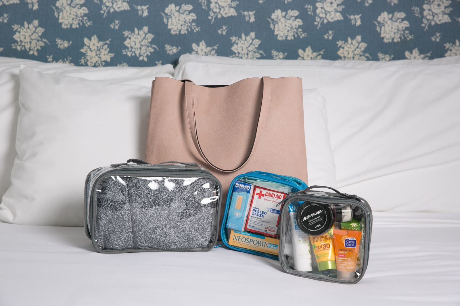 Tote bag and clear packing cubes on a bed