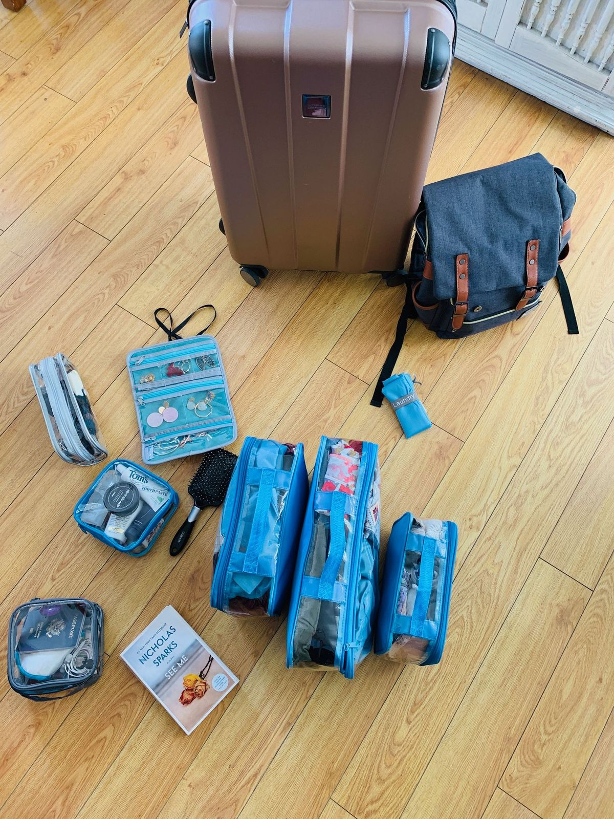 travel essentials organized in turquoise clear packing cubes