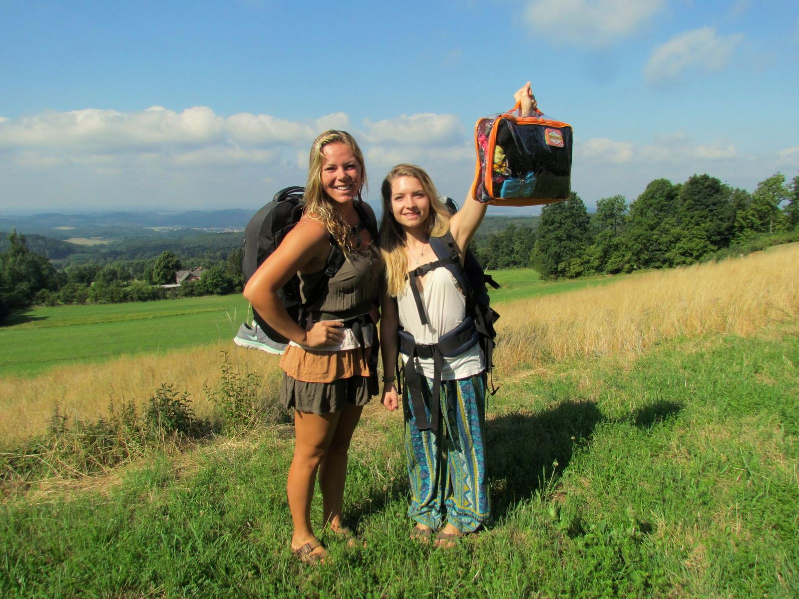 two ladies on a hiking trip with a large orange cube