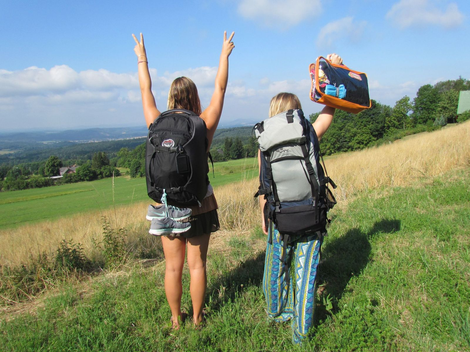 two ladies with backpacks on a hiking trip with a large orange cube