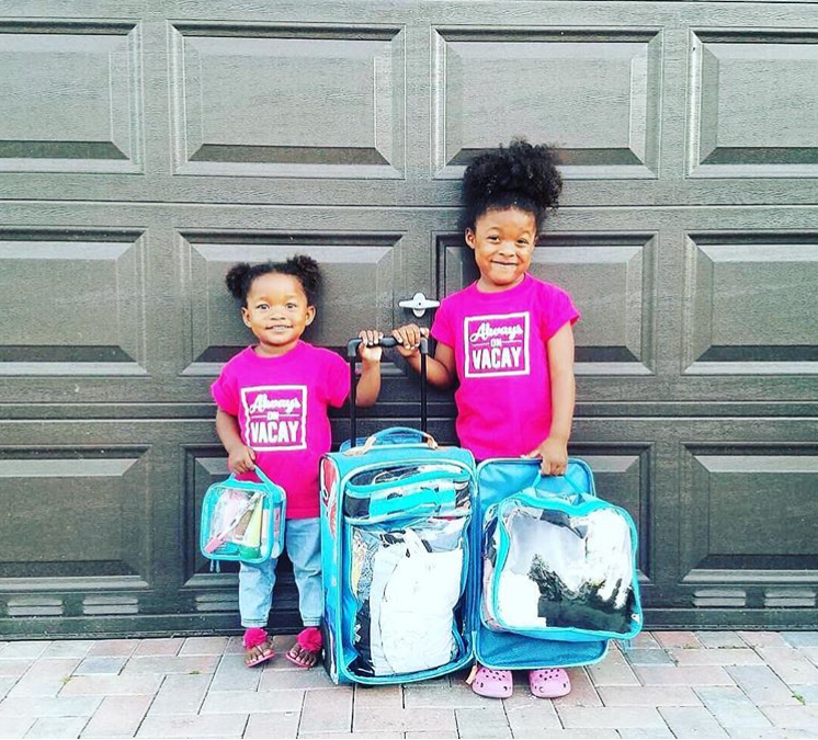 two little girls with a suitcase and packing cubes
